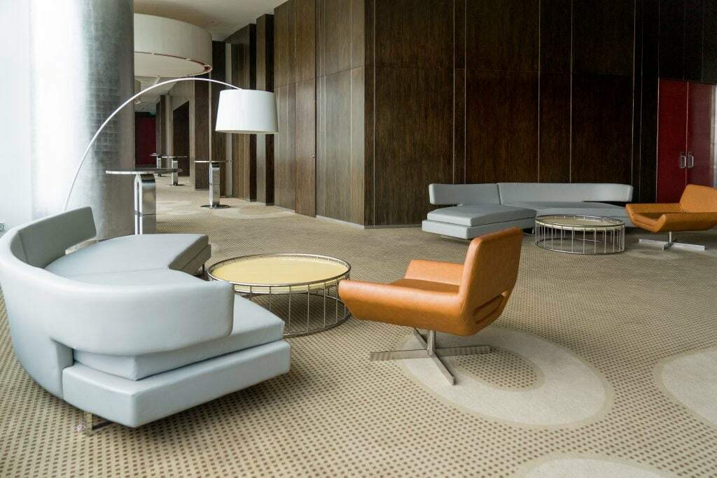 Modern hotel lobby with hallway or office lounge room. Interior with wood paneling, leather sofa and chairs, round metallic tables and floor lamp. Downtown workspace design concept